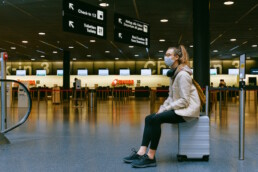 Woman wearing a mask sitting on luggage at an airport