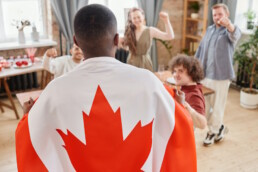 Man wearing a Canada flag on his back at a party surrounded by people
