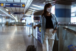 Woman wearing mask in an airport pulling luggage