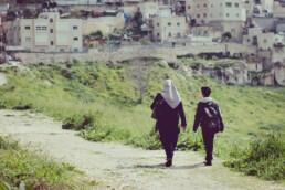 Muslim woman walking with young boy